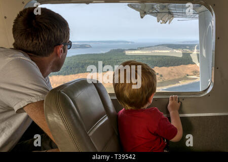 A father & son looking out of the window of a small float plane flying between Seattle and the San Juan Islands. - Stock Image