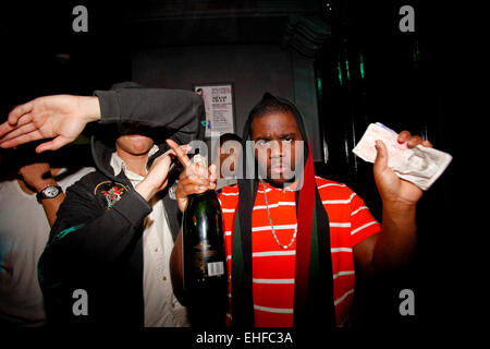 Guys at edge of dancefloor with wads of cash and a bottle of champagne at Bomba at Pacha London 4th April 2010. - Stock Image