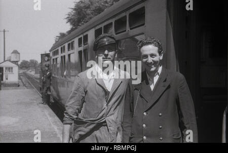 1950, historical, a train driver in a cap and a young train guard or ticket conductor stand together on the railway platform outside a carriage for a picture, England, UK. - Stock Image
