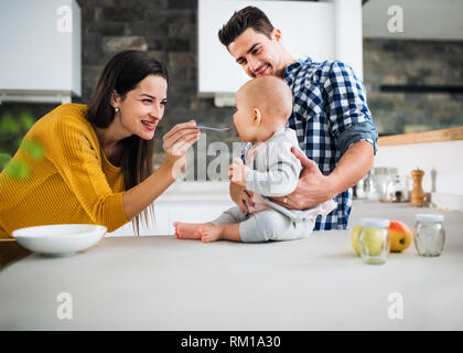 A young family at home, a man holding a baby and a woman feeding her. - Stock Image
