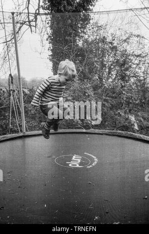 Two year old boy bouncing on a garden trampoline, Medstead, Alton, Hmapshire, England, United Kingdom. - Stock Image