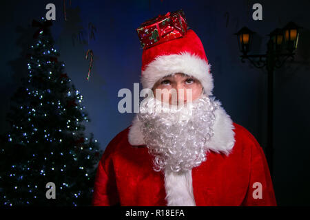 Portrait of smiling good looking male santa smiling while balancing christmas present on his red hat - Stock Image