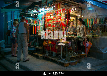Tourists perusing a market shop selling trinkets in Sheung Wan - Stock Image