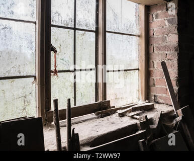 Dusty and cobwebby interior of the Charlecote Watermill, England UK, with light through a grimy window. - Stock Image