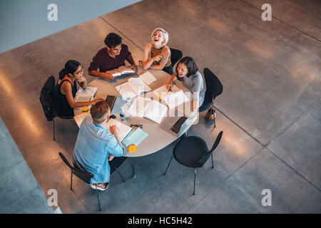 Top view of group of students sitting together at table. University students doing group study and smiling. - Stock Image