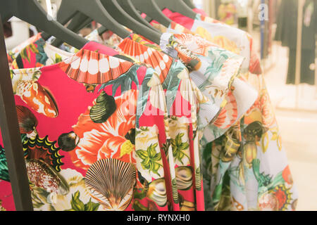 Colorful designer dresses on a rack in a department store. - Stock Image