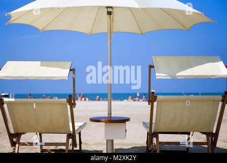 white parasols and sun loungers on a beach in Rimini, Emilia-Romagna, Italy - Stock Image