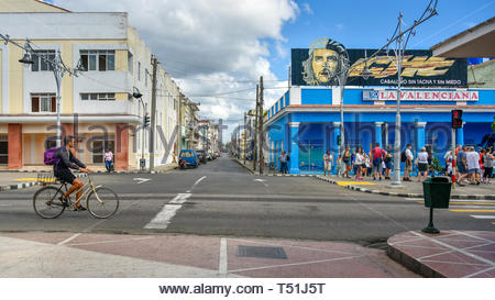 'El Prado' promenade. Everyday lifestyle of Cuban people.  A man rides in bicycle while a group of tourists look a 'Che Guevara' sign on top of a stor - Stock Image