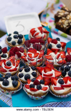 Fresh home made cakes topped with fruit and cream - Stock Image