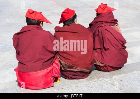 Three young Tibetan Buddhist monks sitting on pavement in Lhasa Tibet - Stock Image