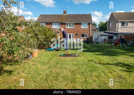 A man mows a lawn in a residential back garden with an electric lawnmower in a sunny day with blue sky in early summer. - Stock Image