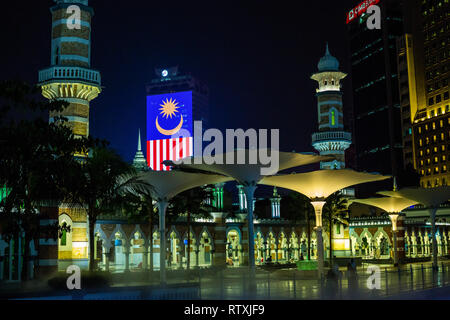 Masjid Jamek (Jamek Mosque) at night, Kuala Lumpur, Malaysia.  Malaysian Flag in background. - Stock Image