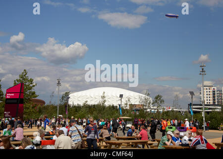 People eating at tables with Basketball Arena in distance on a sunny day at Olympic Park, London 2012 Olympic Games - Stock Image