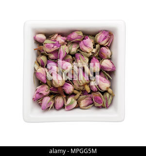 Dried french rosebuds in a square bowl isolated on white background - Stock Image