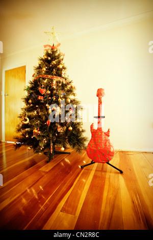 Chrismas wrapped guitar present and tree. - Stock Image
