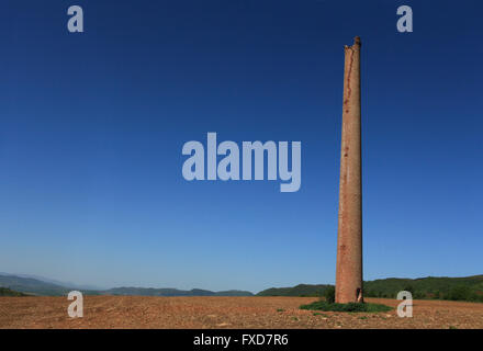 Lonely old chimney in right, the remnants of factory. - Stock Image
