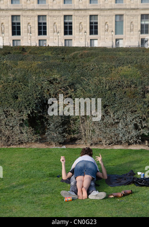 A young couple lying on the grass of the Tuilleries gardens in Paris. Spring. - Stock Image