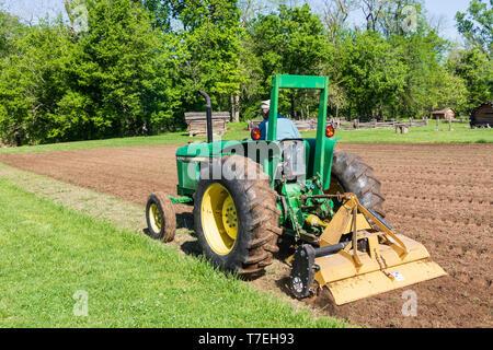LIIMESTONE, TN, USA-4/29/19:  A John Deere tractor tilling a garden at the David Crockett Birthplace State Park. - Stock Image