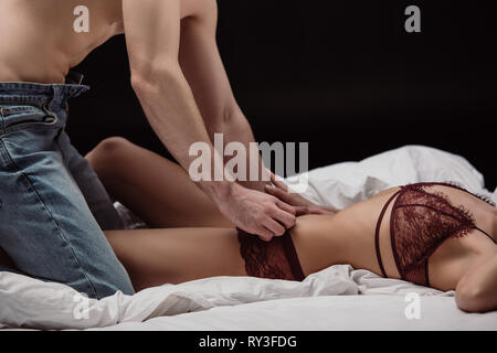 cropped view of man undressing woman in sexy lingerie isolated on black - Stock Image