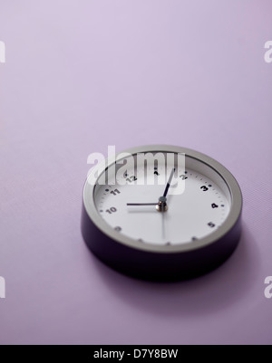 A small wall clock on a light purple wall. - Stock Image