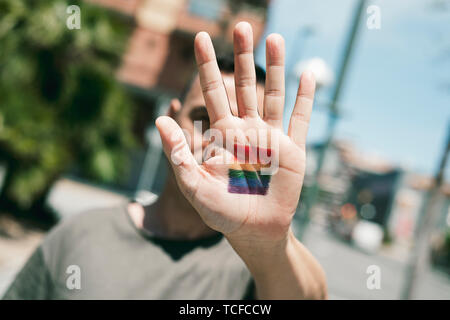 closeup of a young caucasian person with a rainbow flag in the palm of his or her hand, in front of his or her face, on the street at daytime - Stock Image