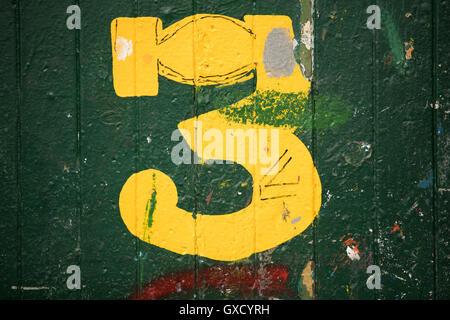 Detail of number 3 green door in ship painters yard - Stock Image