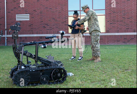 180828-N-RJ834-037  CLEVELAND (Aug. 28, 2018) Navy Diver 1st Class Erik Clark, from Ashland, N.C., attached to Mobile Diving and Salvage Unit (MDSU) 2, demonstrates the operation of an explosive ordinance disposal robot to John Marshall School of Engineering High School students during Cleveland Navy Week in Cleveland, Ohio. The Navy Office of Community Outreach uses the Navy Week program to bring Navy Sailors, equipment and displays to approximately 14 American cities each year for a week-long schedule of outreach engagements designed for Americans to experience firsthand how the U.S. Navy is - Stock Image