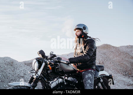 Bearded man with dreadlocks sitting on motorbike smoking electronic cigarette - Stock Image