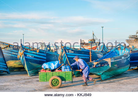 Morocco, Marrakesh-Safi (Marrakesh-Tensift-El Haouz) region, Essaouira. A man pushes a cart past fishing boats in - Stock Image