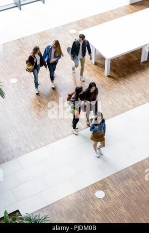 Male and female university students walking and talking in university lobby, high angle view - Stock Image
