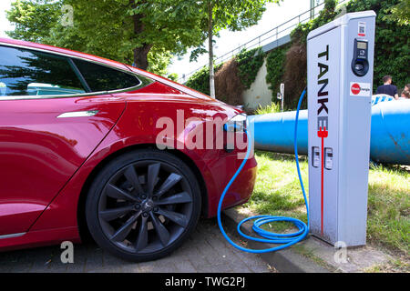 a Tesla Modell S at a charging station of the Mobilstation on the Charles-de-Gaulle square in the district Deutz, Cologne, Germany. With a direct conn - Stock Image