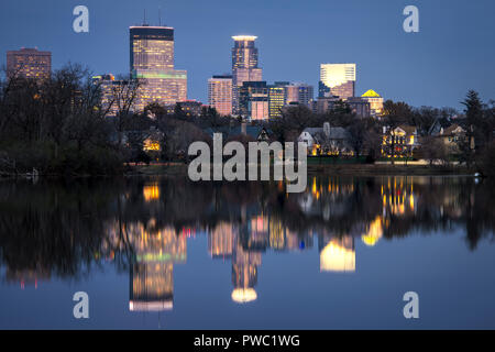 Minneapolis skyline reflected in the calm water of Lake of the Isles in late fall. - Stock Image