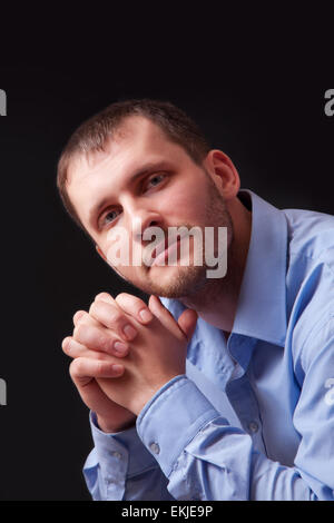 Fashion young man in a blue shirt, portrait on black background - Stock Image
