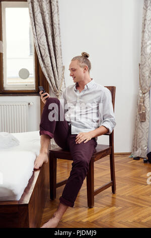 Young man sitting on bedroom chair looking at smartphone - Stock Image