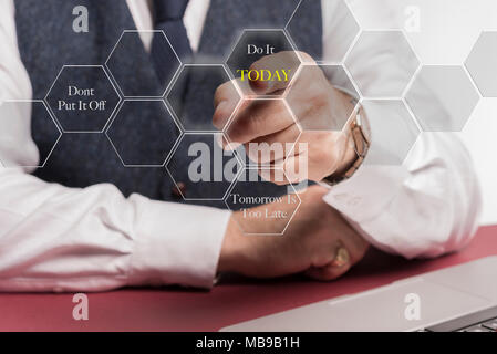 """A smartly dressed business man sitting at a desk whilst pushing a virtual button on the screen saying """" dont put ot off, do it today,  tomorrow is too - Stock Image"""