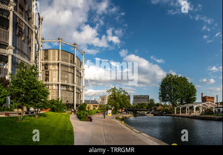 London, England, UK - June 3, 2019: Pedestrians and cyclists travel along the Regents Canal towpath beside the Gasholders buildings in the King's Cros - Stock Image