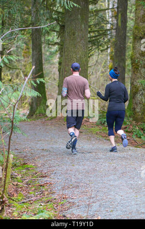 Young couple running on a trail in a forested area of Cliff Falls Park, Maple Ridge, B. C. - Stock Image