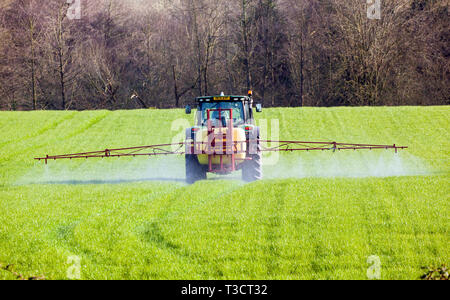 Tractor with a farmer driving crop spraying chemicals and pesticides in a field in the rural English agricultural countryside - Stock Image
