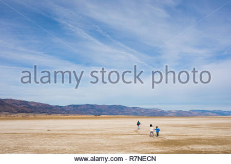 Three young kids run across the mineral and salt flats of the dry lake bed at Middle Alkali Lake near Cedarville California. - Stock Image