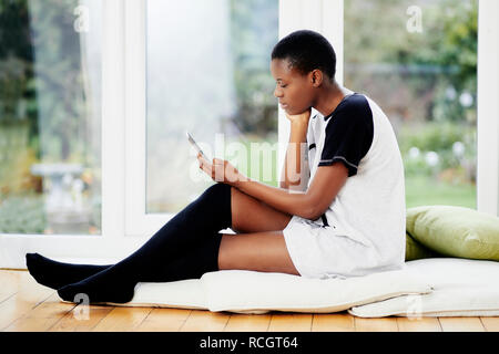 Ethnic girl relaxing looking at her phone - Stock Image
