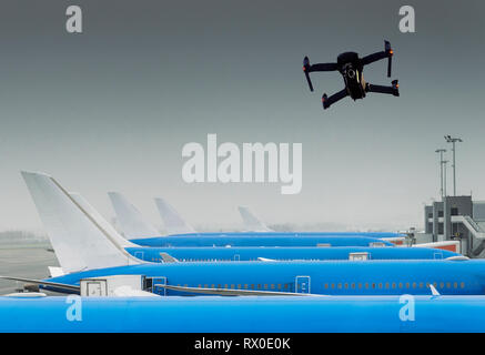Unmanned drone flying near row of commercial airplanes at airport, flight disruption concept - digital composite. - Stock Image