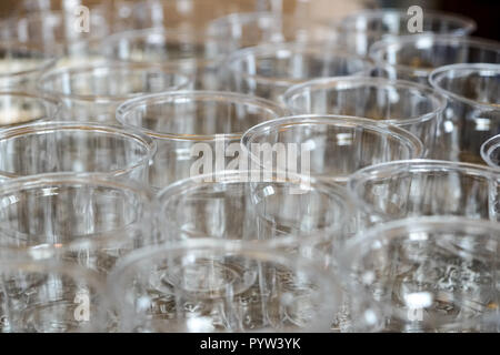 Closeup of a many glasses on a table, with focus selective on front edge of glass. - Stock Image