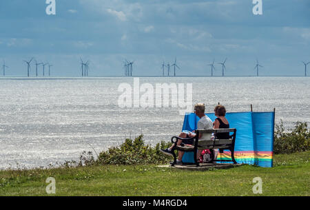 Couple picnic with a view of windfarms off Clacton on Sea - Stock Image