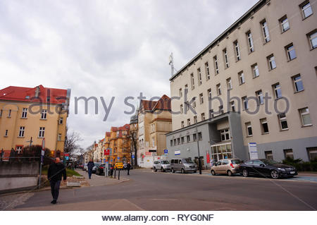 Poznan, Poland - March 8, 2019: People and parked cars on the Slowackiego street in the city center. - Stock Image