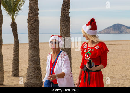 Benidorm, Costa Blanca, Spain, 25th December 2018. British tourists dress for the occasion on Christmas Day in this favourite getaway destination for Brits escaping the cold weather at home. Temperatures will be in the mid to high 20's Celsius today in this mediterranean hotspot. Two women wearing Christmas clothing strolling on Levante beach promenade. - Stock Image