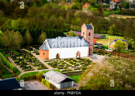 Danish church with a cemetary in a small village surrounded by trees seen from above - Stock Image