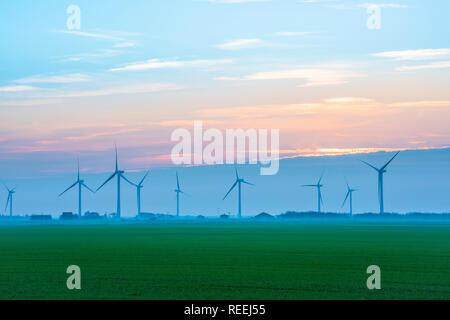 Wind power UK, view across a Cambridgeshire fen towards a row of wind turbines, England, UK. - Stock Image