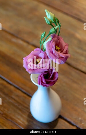 One white small mini vase with pink flower on wooden table, decorative floral background - Stock Image