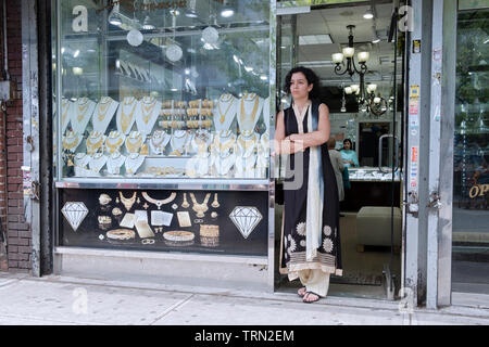 An attractive woman in a sari in deep thought outside the store where she works. Diversity Plaza, Jackson Heights, Queens, New York City. - Stock Image