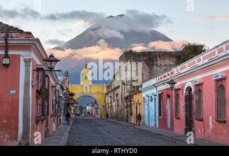 Colonial Architecture and Street Scene during Early Morning Sunrise in Antigua Guatemala with Santa Catalina Arch and Agua Volcano in the Background - Stock Image